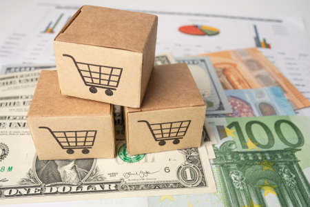Shopping cart on box with US dollar and Euro banknotes background, Banking Account, Investment Analytic research data economy, trading, Business import export online company concept.
