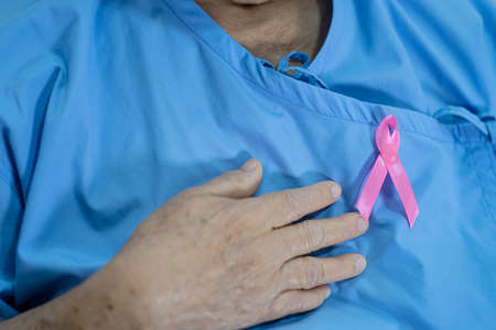 Breast cancer, pink ribbon at Asian senior lady patient for supporting awareness. 免版税图像