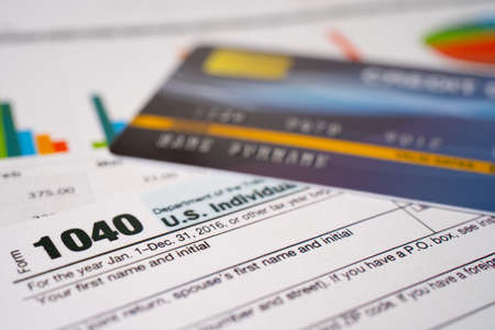 Tax Return form 1040 with credit card on graph, U.S. Individual Income.