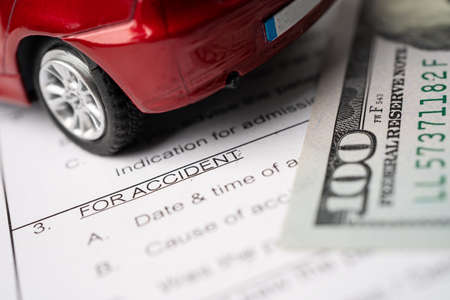 Car and US dollar banknotes on Insurance claim accident car form background, Car loan, Finance, saving money, insurance and leasing time concepts.
