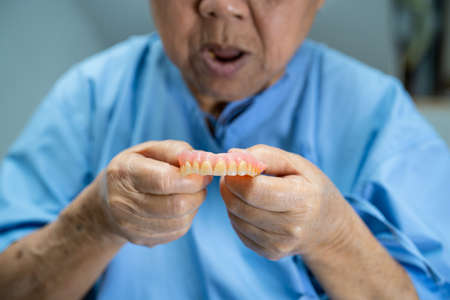 Asian senior or elderly old woman patient holding to use denture in nursing hospital ward, healthy strong medical concept 免版税图像