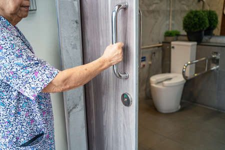 Asian senior elderly old lady woman patient open toilet bathroom by hand in nursing hospital ward, healthy strong medical concept. 免版税图像