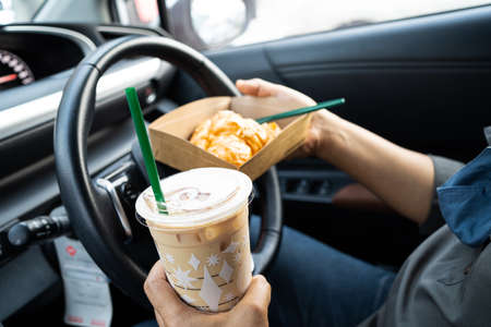 Asian lady holding ice coffee and bread bakery in car dangerous and risk an accident.