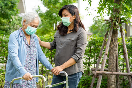 Asian senior or elderly old lady woman walk with walker and wearing a face mask for protect safety infection and kill Novel Coronavirus Covid-19 virus. 免版税图像