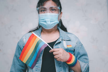 Asian lady wearing blue jean jacket or denim shirt and holding a rainbow color flag