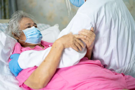 Doctor help and check Asian senior or elderly old lady woman patient wearing a face mask in hospital for protect infection Covid-19 Coronavirus.