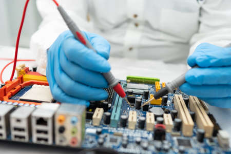Technician repairing inside of hard disk by soldering iron. Integrated Circuit. the concept of data, hardware, and technology. 免版税图像