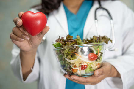 Nutritionist doctor holding various healthy fresh vegetables for patient.