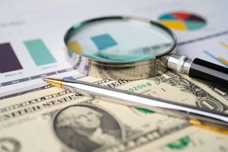 Magnifying glass and US dollar banknotes background, Banking Account, Investment Analytic research data economy, trading, Business company concept.