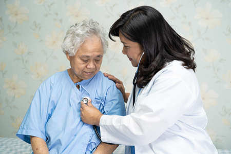 Doctor using stethoscope to checking the patient sit down on a bed in the hospital ward, healthy strong medical concept