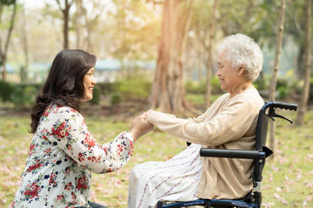 Asian senior or elderly old lady woman patient with care, help and support on wheelchair in park in holiday, healthy strong medical concept.