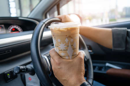 Asian lady holding ice coffee for drink food in car dangerous and risk an accident.