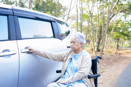 Asian senior or elderly old lady woman patient sitting on wheelchair prepare get to her car, healthy strong medical concept.