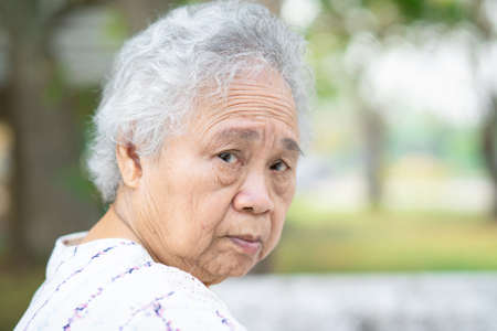 Asian senior or elderly old lady woman sitting in park, healthy strong medical concept.