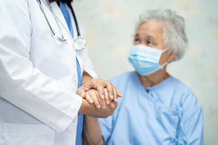 Doctor holding hand of Asian woman patient wearing face mask for protect Covid-19 Coronavirus.