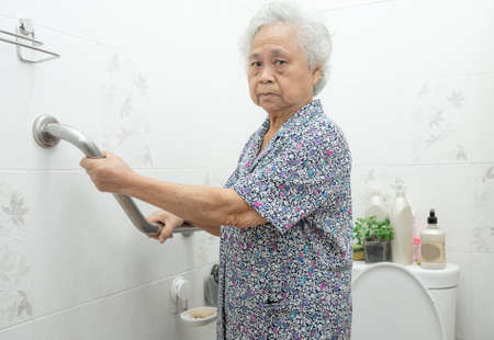 Asian senior or elderly old lady woman patient use toilet bathroom handle security in nursing hospital ward, healthy strong medical concept.
