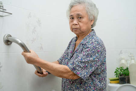 Asian senior or elderly old lady woman patient use toilet bathroom handle security in nursing hospital ward, healthy strong medical concept. Imagens