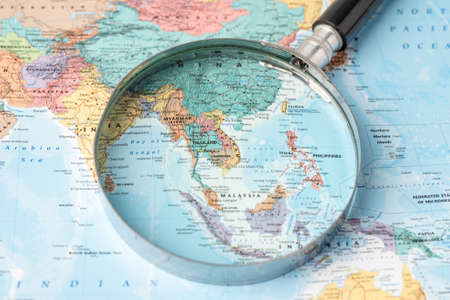 Bangkok, Thailand - November 01, 2020 Asia, Magnifying glass close up with colorful world map