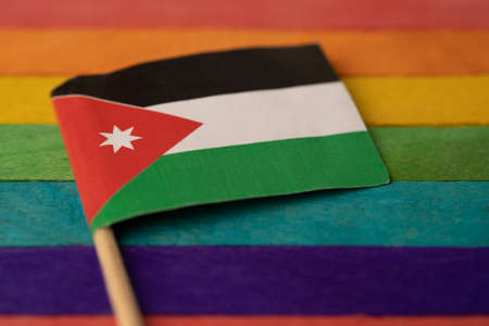 Jordan flag on rainbow background symbol of LGBT gay pride month  social movement rainbow flag is a symbol of lesbian, gay, bisexual, transgender, human rights, tolerance and peace.