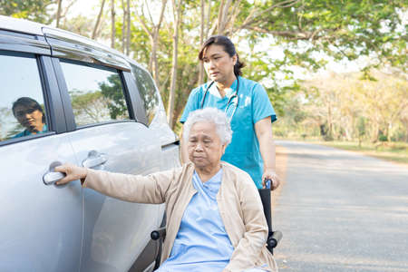 Help and support asian senior or elderly old lady woman patient sitting on wheelchair prepare get to her car : healthy strong medical concept. Stock fotó