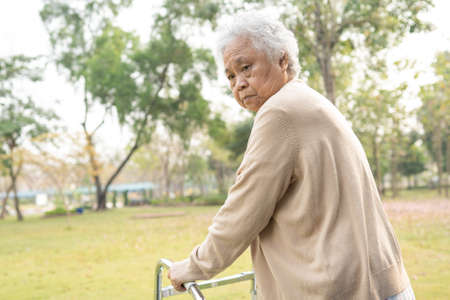 Asian senior or elderly old lady woman patient walk with walker in park with copy space, healthy strong medical concept
