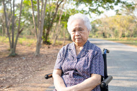 Asian senior or elderly old lady woman patient on wheelchair in park, healthy strong medical concept. Stock fotó