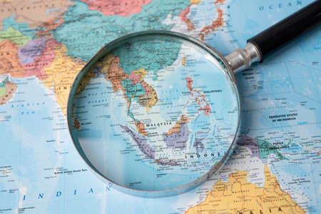 Bangkok, Thailand - August 01, 2020 Asia, Magnifying glass close up with colorful world map