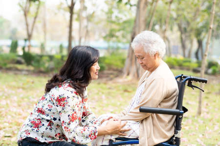 Asian senior or elderly old lady woman patient with care, help and support happy on wheelchair in park in holiday, healthy strong medical concept.
