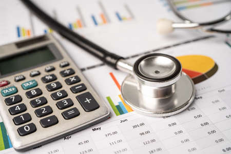 Stethoscope with calculator on chart graph paper, finance, account, statistic, analytic economy Business concept.