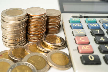 Coins on calculator and graph  paper. Finance development, Banking Account, Statistics, Investment Analytic research data economy, Stock exchange trading, Business company concept.