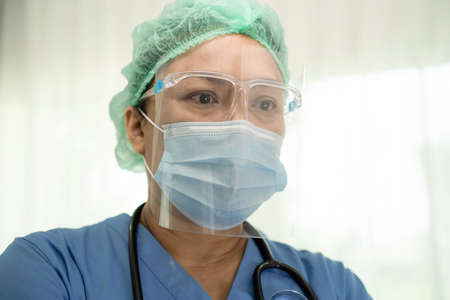 Asian doctor wearing face shield and PPE suit new normal to check patient protect safety infection Covid 19 Coronavirus outbreak at quarantine nursing hospital ward.
