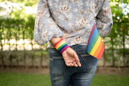 Asian lady holding rainbow color flag, symbol of LGBT pride month celebrate annual in June social of gay, lesbian, bisexual, transgender, human rights.
