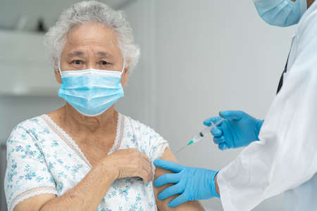 Elderly Asian senior woman wearing face mask getting covid-19 or coronavirus vaccine by doctor make injection. Stock fotó