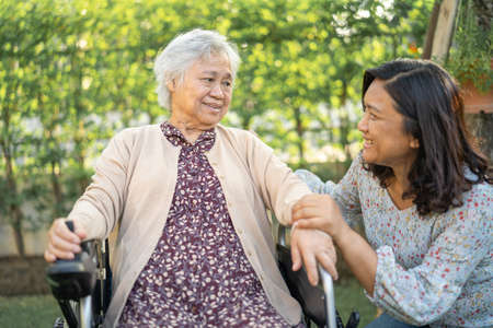 Help and care Asian senior or elderly old lady woman patient sitting on wheelchair at park in nursing hospital ward, healthy strong medical concept.