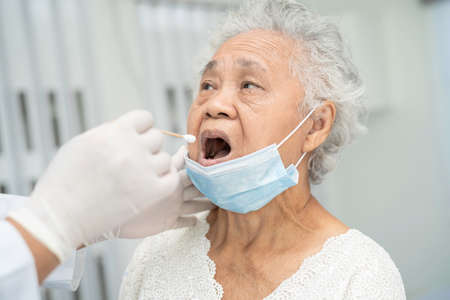 Doctor in pep suit taking a throat and nasal swab from senior asian woman patient to test covid-19 coronavirus infection.