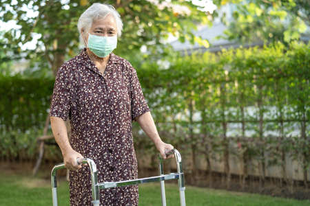 Asian senior or elderly old lady woman patient walk with walker in park,  healthy strong medical concept. Stock fotó