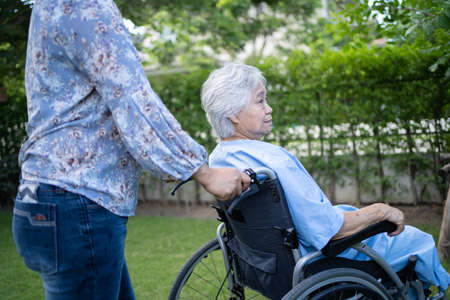 Doctor help and care Asian senior or elderly old lady woman patient sitting on wheelchair at park in nursing hospital ward, healthy strong medical concept. Stock fotó