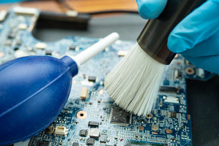 Technician use brush and air blower ball to clean dust in circuit board computer. Repair upgrade and maintenance technology.