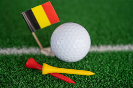 Golf ball with Germany flag and tee on green lawn or grass is most popular sport in the world.