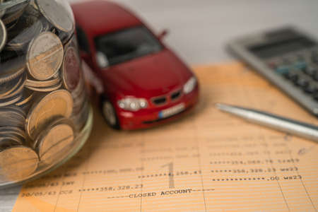 Car and calculator with coins on bookbank background, Car loan, Finance, saving money, insurance and leasing time concepts. coins, Car loan, Finance, saving money, insurance and leasing time concepts.