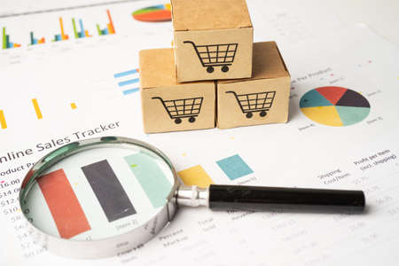 Shopping cart  on box with magnifying glass on graph background. Banking Account, Investment Analytic research data economy, trading, Business import export transportation online company concept. Stock fotó