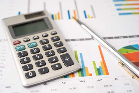 Calculator with pen on chart graph paper, finance, account, statistic, analytic economy Business concept.