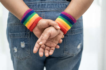 Asian lady wearing rainbow flag wristbands, symbol of LGBT pride month celebrate annual in June social of gay, lesbian, bisexual, transgender, human rights. Stock fotó