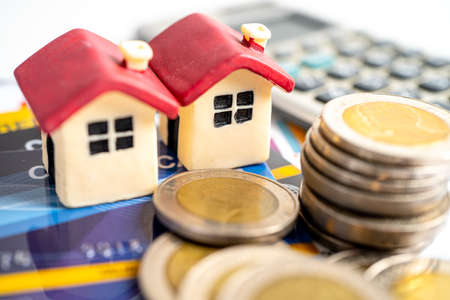 House model on credit card, coin and calculator, installment payment concept. Stock fotó