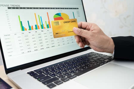 Asian accountant working, calculate and analyzing report project accounting with notebook and credit card in modern office, finance and business concept.