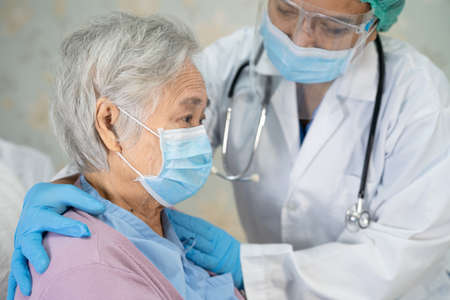 Doctor checking Asian senior or elderly old lady woman patient wearing a face mask in hospital for protect infection Stock fotó