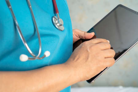 Doctor holding digital tablet to search data for treat patient in nursing hospital ward, healthy strong medical concept.