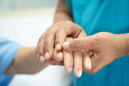 Holding hands Asian senior or elderly old lady woman patient with love, care, encourage and empathy at nursing hospital ward, healthy strong medical concept