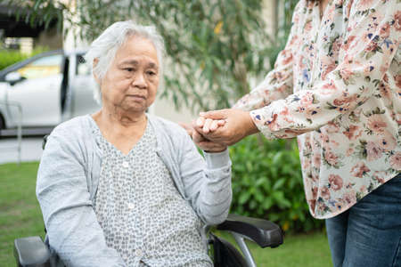 Help Asian senior or elderly old lady woman on wheelchair and wearing a face mask for protect safety infection  in park. Stock fotó