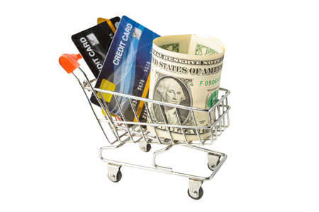 Credit card and US dollar banknotes in shopping cart isolated on white background, finance concept.